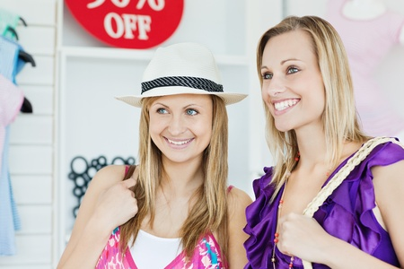 Confident women choosing clothes together photo