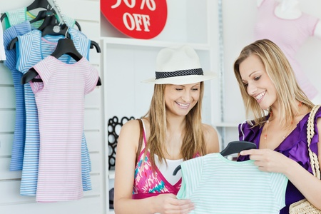 Cute young women choosing clothes together photo