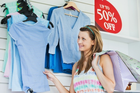 Delighted woman choosing clothes photo