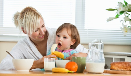Pretty mother and daughter having breakfast photo