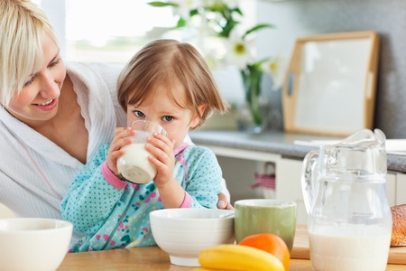 Blond mother and daughter having breakfast Stock Photo - 10248938