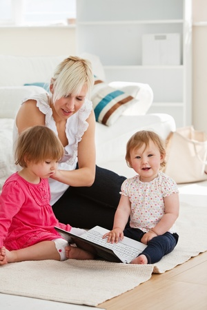 Good-looking woman working with her children at laptop Stock Photo - 10248589
