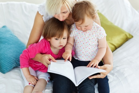 Cute mother reading a book with children photo