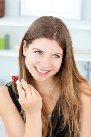 Beautiful girl using lipstick photo