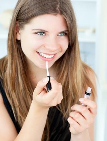 Smiling girl using lipstick Stock Photo - 10246456