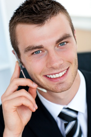 Charming businessman using his mobile phone in office photo