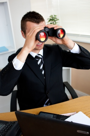 Businessman using binoculars photo