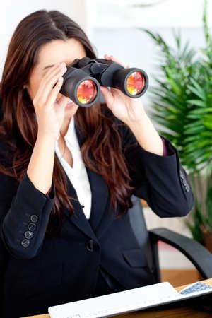 Young businesswoman using binoculars photo