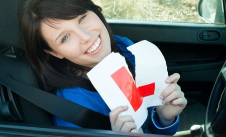learner: Cheerful young female driver tearing up her L sign  Stock Photo