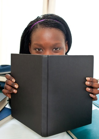 Cute afro-american teenager behind a book looking at the camera photo