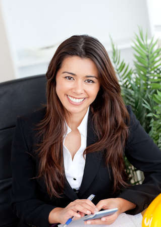 Smiling asian businesswoman using a calculator  photo