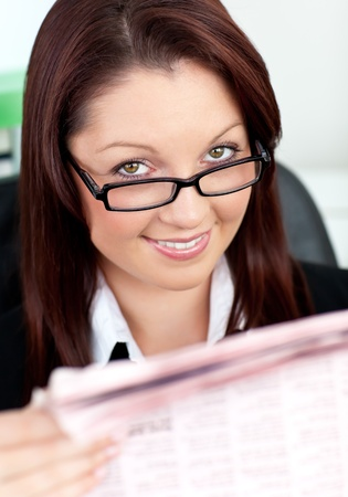 Smiling businesswoman reading a newspaper  photo