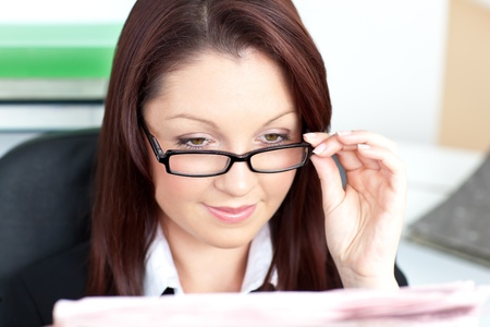 Delighted businesswoman reading a newspaper wearing glasses  photo
