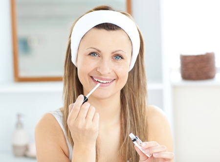 Glowing woman applying gloss on her lips wearing a headband  photo