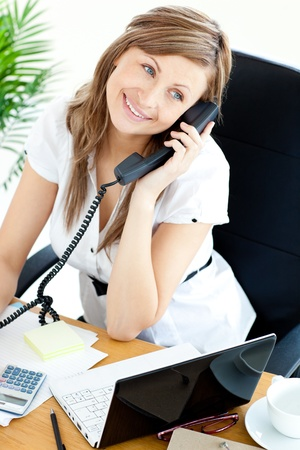Bright businesswoman talking on phone sitting in her office photo