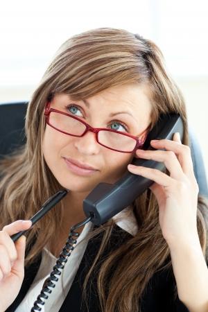 Pensive businesswoman talking on phone wearing glasses Stock Photo - 10248897