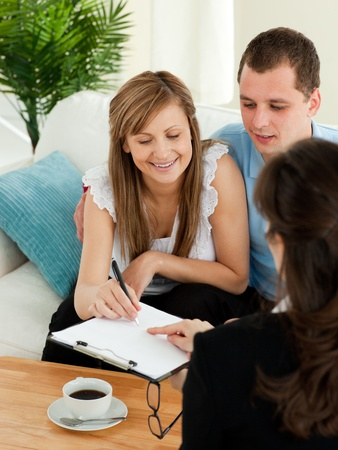Bright young couple signing a contract sitting in their living room  photo