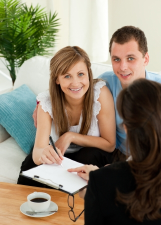 Loving young couple signing a contract sitting in the living room photo