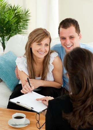 vendedores: Feliz pareja joven firma un contrato sentado en la sala de estar Foto de archivo