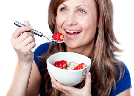 Positive young woman eating cereals with strawberries photo