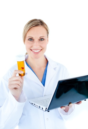 Smiling young doctor holding a laptop and pills photo
