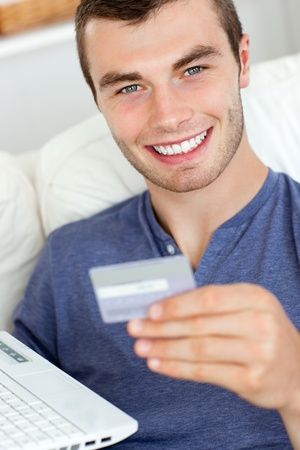 Close-up of a jolly man holding a card and a laptop photo