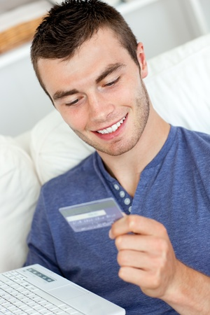 Attractive young man holding a card and a latop sitting on the sofa  photo