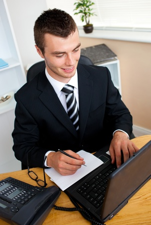 Animated young businessman using his laptop writing on a paper Stock Photo - 10249812