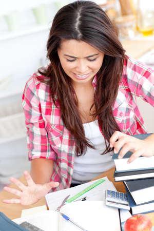 learning by doing: Frustrated asian student doing her homework  Stock Photo