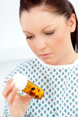 Caucasian female patient looking at pills  Stock Photo - 10250336