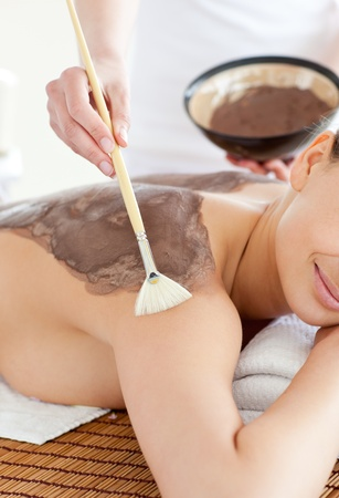beauty treatment clinic: Charming woman enjoying a mud skin treatment