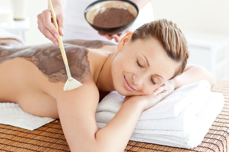 beauty treatment clinic: Relaxed woman enjoying a mud skin treatment  Stock Photo