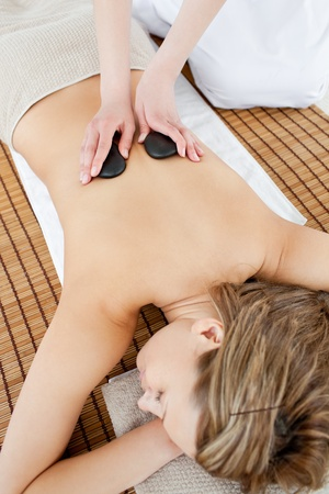 beauty treatment clinic: Pretty woman lying on a massage table having a stone therapy