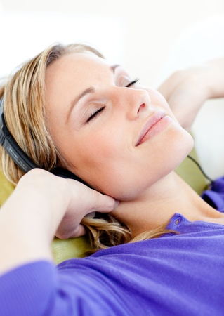 Relaxed woman listen to music lying on a sofa  photo