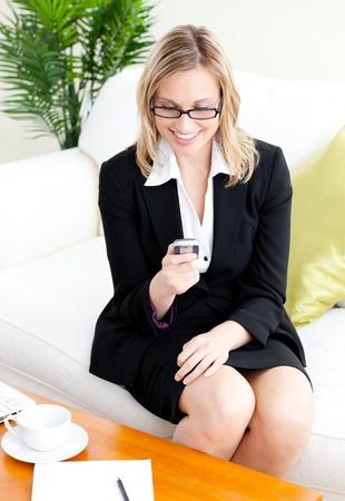 Verheugd businessowman met behulp van haar mobiele telefoon siiting op een sofa