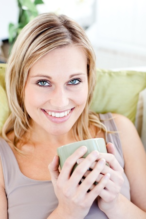 Positive blond woman holding a cup smiling at the camera photo