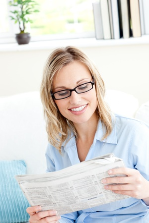 Attractive businesswoman reading the newspaper sitting on the sofa photo