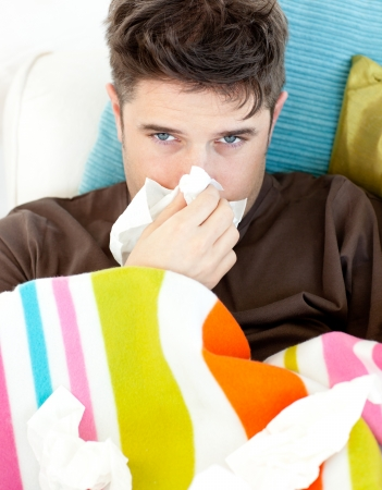 Diseased young man with tissues lying on the sofa Stock Photo - 10247684