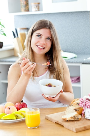 Glowing brunette woman eating cereals with raspberrie in the kitchen photo