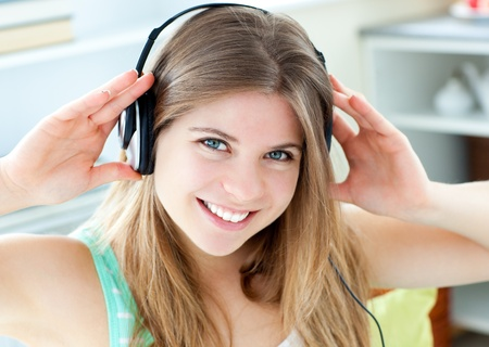 Jolly caucasian woman listen to music with headphones in the kitchen photo