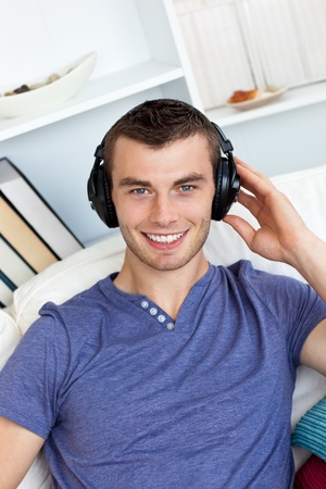 Smiing caucasian man listen to music with headphones  photo