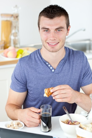 Handsome man eating croissant drinking coffee  photo