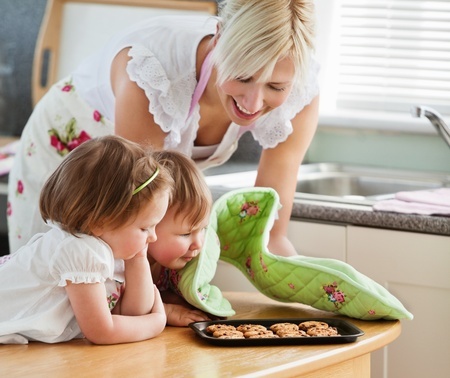 baking cookies: Sorridente cookie cottura donna con le sue figlie  Archivio Fotografico