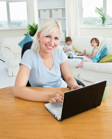 Blond mother using laptop photo