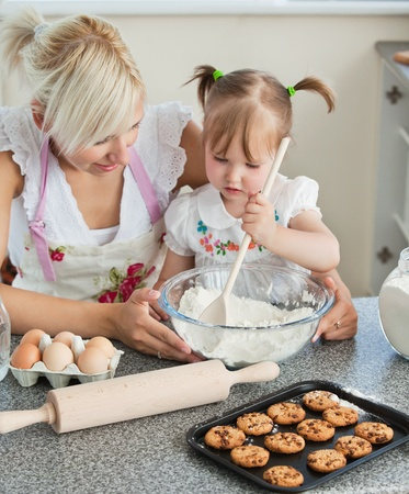 Smiling woman baking cookies with her daughters Stock Photo - 10248940