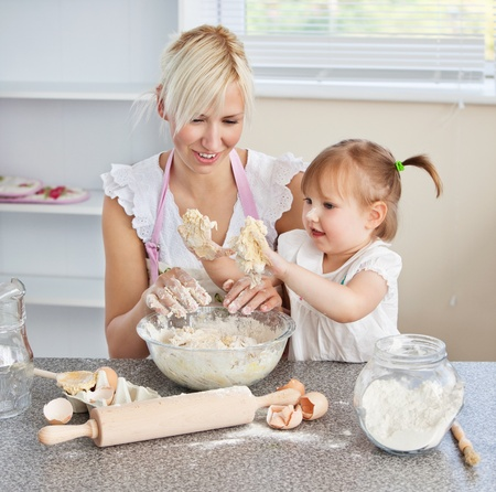 Simper woman baking cookies with her daughter photo