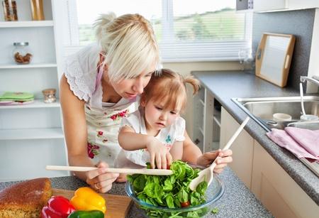 ni�os enfermos: Madre e hija prepara una ensalada Foto de archivo