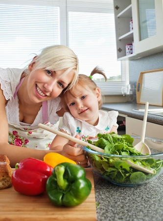 Smiling mother and daughter preparing a salad in kitchen photo