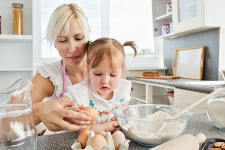 Focused woman baking cookies with her daughter photo