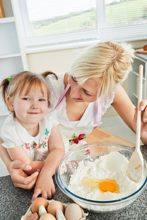Cute woman baking cookies with her daughter photo